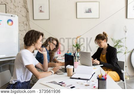 Group Of Young Women Dreamily Working On Laptop At Work. Beautif