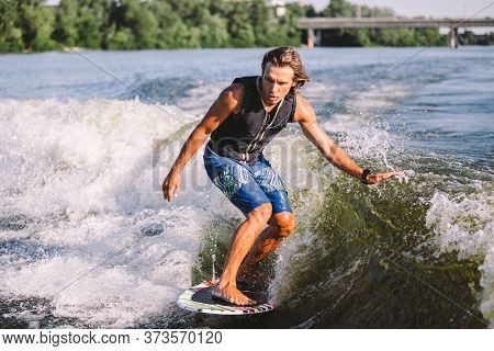Young Athletic Man With Long Hair Wakesurfing On Waves Of River In Sunny Summer Weather. Ttheme Outd