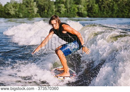 Active Wakesurfer Jumping On Wake Board Down The River Waves. Surfer On Wave. Male Athlete Training
