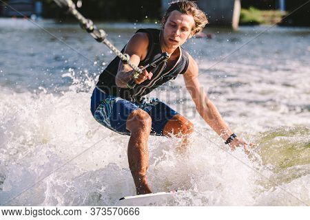 Beautiful Long Haired Blond Wakesurf In Vest On Board Along Waves Of Lake. Athletic Male Athlete Wak