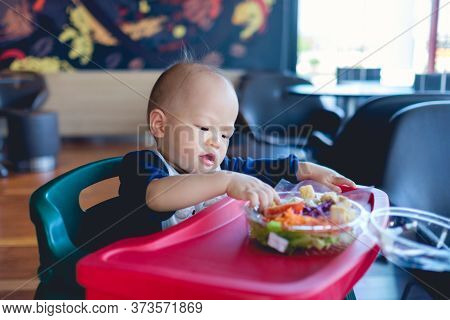 Happy Smiling Little Asian Toddler Baby Boy Sitting In High Chair Eating Salad At Restaurant,healthy