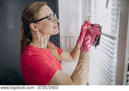 Mature Housewife Removing Dust From Jalousie On Window