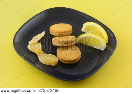 Cookies With Lemon Ginger Cream Filling  With Lemon Wedges And Crystallized Ginger On Dark Blue Snac