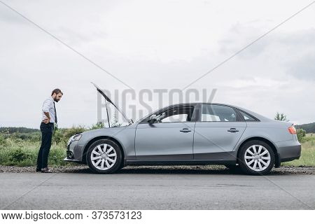 Stressed Man Looking For Failure Cause Under Car Hood