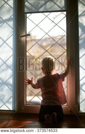 Small Girl Looking Through The Window With Lattice Outside. Staying At Home Because Of Carantin.