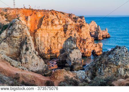 Rocky Cliffs And A Lighthouse At Ponta Da Piedade Near Lagos, Portugal
