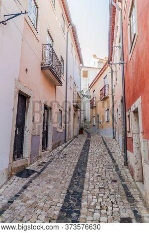 Narrow Alley In Alfama Neighborhood Of Lisbon, Portugal