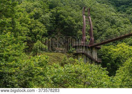 End Of Large Suspension Footbridge Bridge Over Treetops Of Lush Verdant Trees In Mountain Recreation