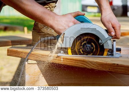 Builder Saws A Board With A Circular Saw In The Cutting A Wooden Plank