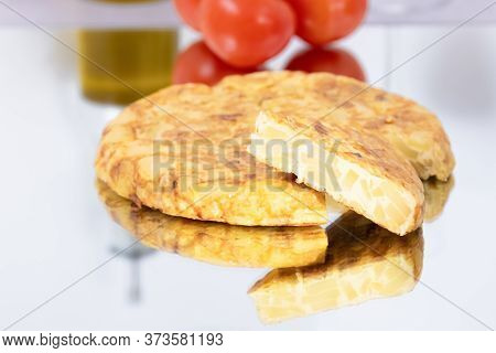 Close-up Of A Tasty Looking Spanish Omelet With A Slice Taken Out On A Glass Table With Some Out Of
