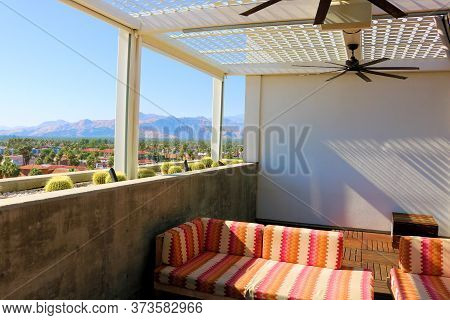 June 22, 2020 In Palm Springs, Ca:  Outdoor Rooftop Deck With Fans Above Chairs And Sofas Besides Ma