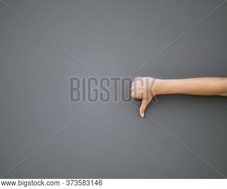 Womens Right Hand Showing Thumb Down Dislike Isolated On Gray Background.
