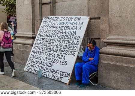 Madrid, Spain - October 25, 2017: Homeless Man With A Big Sign In The Center Of Madrid.