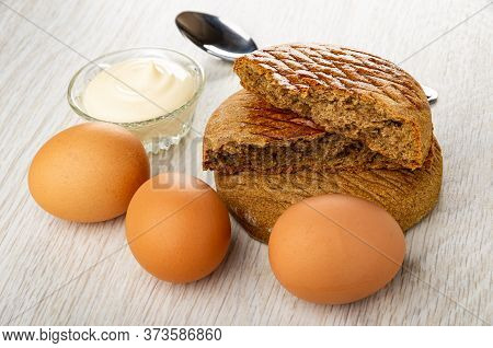 Transparent Bowl With Mayonnaise, Teaspoon, Brown Unpeeled Boiled Eggs, Rye Flapjacks On Wooden Tabl