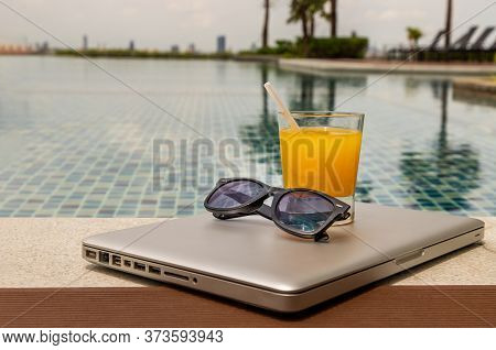 Relaxing Moment By The Pool. Take A Break From Working On Laptop And Enjoy The Fresh Orange Juice Fo