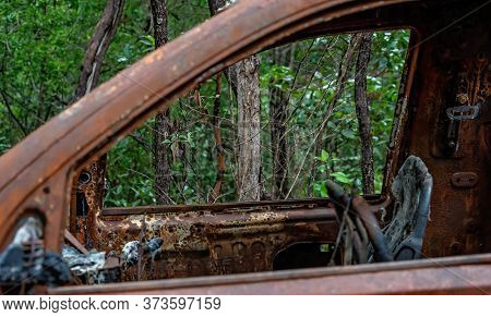 Looking Through The Window Into The Burnt Out Interior Of A Burnt Out Car Wreck Abandoned On A Mount