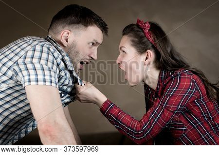 Close-up Of Husband And Wife Who Curse At Home In The Evening. Wife Pats Husband Over Shirt Collar