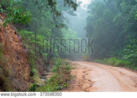 A Rough Dirt Track Leading Up A Mountain On An Afternoon Misted By Rain