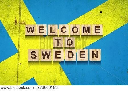 Welcome To Sweden. The Inscription On Wooden Blocks On The Background Of The Flag Of Sweden. Travels