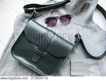 Green Leather Women Bag, Grey Knitted Sweater,  Top View, Flat Lay. Fashionable Women's Accessories.