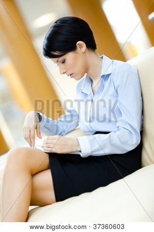 Busy business woman rests at the sofa reading book at the hall