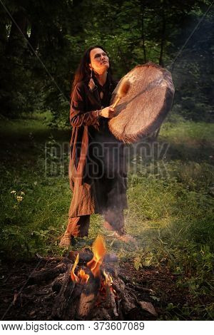 Woman Dressed In Shaman Costume Playing On Shaman Frame Drum Near Large Fire In Forest At Dusk