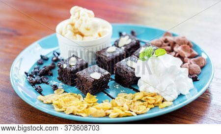 Vanilla Ice-cream And Brownies On A Blue Plate.