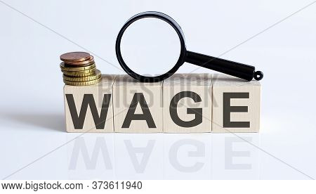 The Wage Sign On A Wooden Block On White Background With Coins And Magnifier