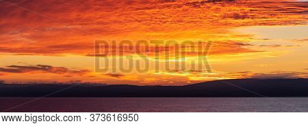 Scenic Red-and-orange Sunset With A Shoreline As A Silhouette In The Foreground. Amazing Panorama.