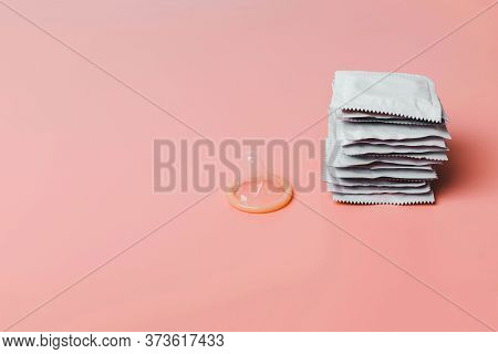 Condom On A Pink Background. The Concept Of Safe Sex, Stopping The Transmission Of Sexually Transmit