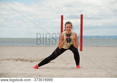 Fit Healthy Woman Wearing Sportswear Training Legs And Glutes With Kettlebell. Weightlifting Workout