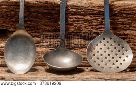 Used And Old Kitchen Utensils On Wooden Background