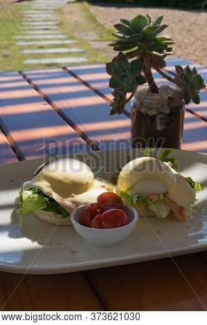Eggs Benedict With Hollandaise Sauce And Salmon Served With Halved Cherry Tomatoes. Outdoor Al Fresc
