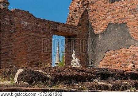 Buddha Statue Figurines, Small Sculptures With Old Ruins On The Background. Ancient Ruins Of Ayuttha