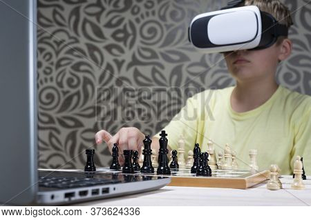 A Boy In A Virtual Reality Headset Plays Chess With A Laptop. Learning To Play Chess Using Informati