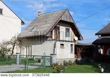 Unusual Looking Small Suburban Family House With Wooden Front Porch And Tall Pointy Roof Surrounded