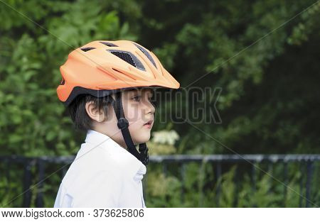 Healthy Child Boy Wearing A Bike Helmet, Outdoors Portrait Happy Kid With Smiling Face Wearing A Cyc