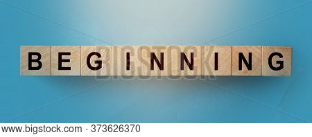 Text Beginning On Wooden Cubes. Cubes Lay On A Blue Gradient Background. Startup Business Concept