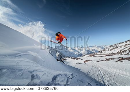 Athlete Male Skier Jumps From A Snow-covered Slope Against The Backdrop Of A Mountain Landscape Of S