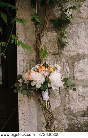 Bridal Bouquet Of White Peonies, Cream Roses, Orange Buttercups And Branches Of Eucalypt Tree On Nea