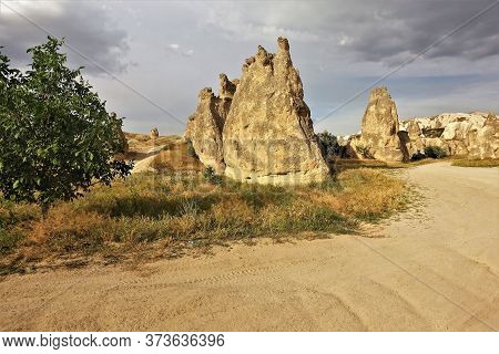The Amazing Landscape Of Cappadocia. A Summer Day, Against The Background Of A Cloudy Sky And Dried