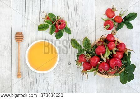 Immune boosting rosehip berry fruit used in herbal medicine for cold and flu remedy drink with honey. Health food very high in antioxidants and vitamin c. Flat lay on rustic wood background.