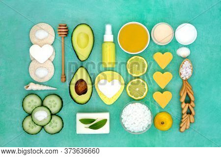 Skincare anti ageing beauty treatment with lemon, cucumber and avocado, with spa moisturising, ex foliation and cleansing products. Flat lay on mottled green background.