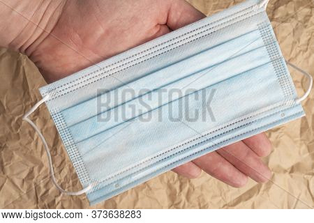 Medical Protective Surgical Mask In Hand On A Background Of Crumpled Wrapping Brown Paper. Close-up