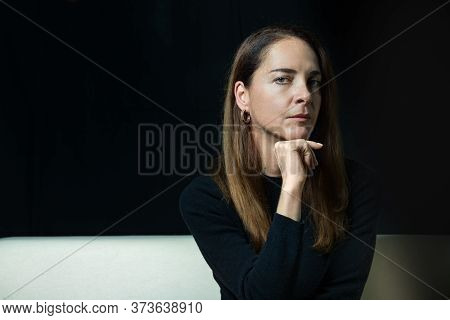 Portrait Of A Mature Woman 45 - 50 Years, Serious, Pensive, Looking Camera With Hand On Chin Over Bl