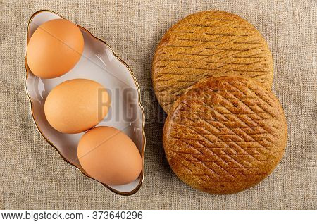 Brown Unpeeled Boiled Eggs In White Bowl, Two Rye Flapjacks On Burlap. Top View