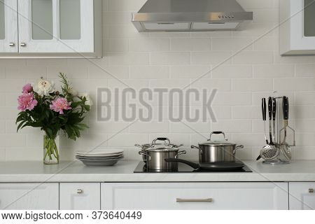 Kitchen Counter With Set Of Dishware, Utensils And Beautiful Bouquet. Interior Design