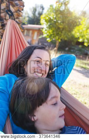 A Boy With His Mother Are Lying In A Hammock In The Courtyard Of The House. A Woman Spends Time With