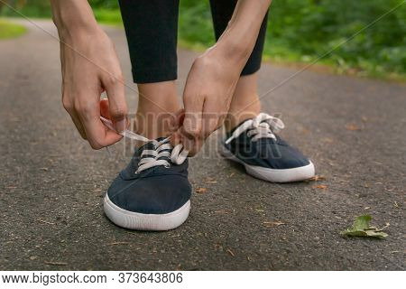 Close-up Of Women's Hands Tying Shoelaces In Dark Blue Sneakers On A Jog In The Woods.