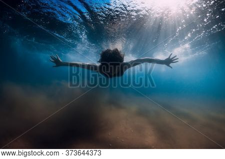 Woman Dive Without Surfboard Under Ocean Wave. Underwater Duck Dive Under Wave And Sandy Bottom
